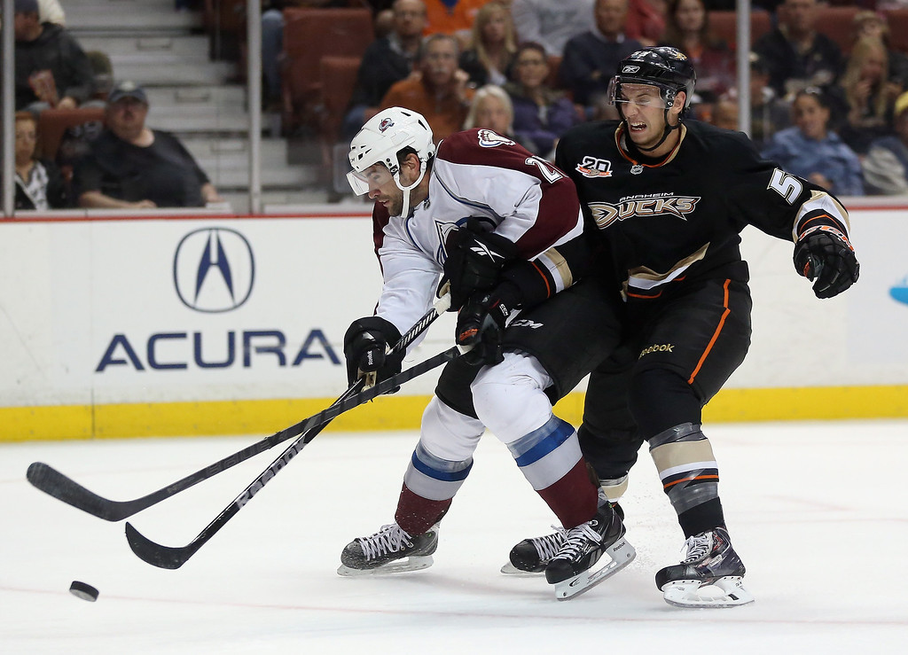 . Guillaume Desbiens #27 of the Colorado Avalanche is pursued by Shea Theodore #53 of the Anaheim Ducks for the puck in the second period at Honda Center on September 22, 2013 in Anaheim, California.  (Photo by Jeff Gross/Getty Images)