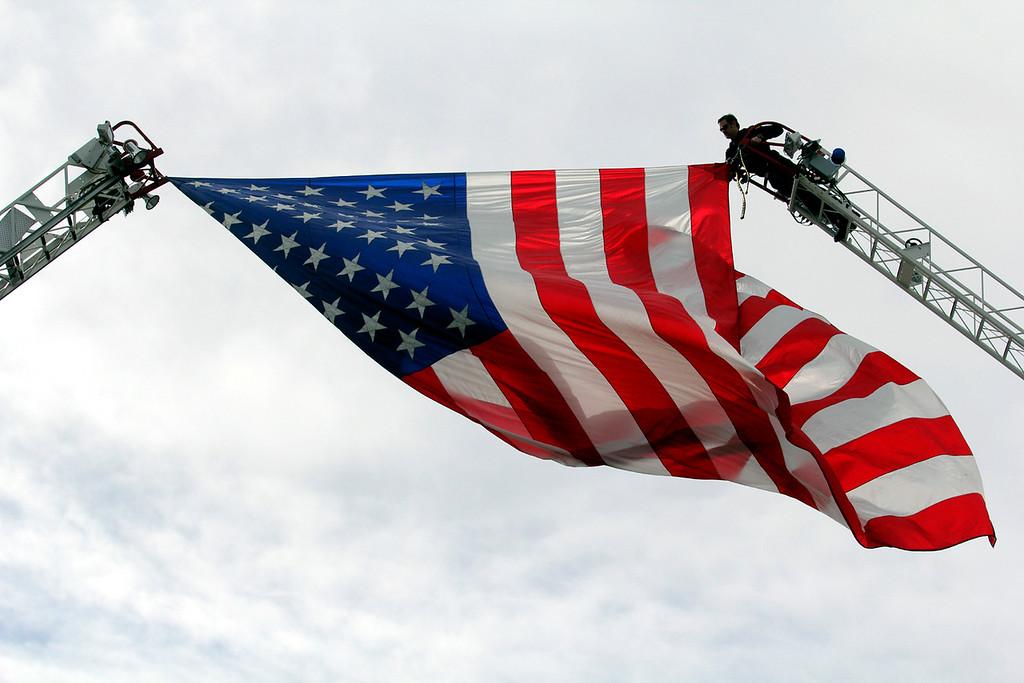 . A San Jose firefighter adjusts a large flag flying over Santa Clara Street for Thursday\'s memorial. (Shmuel Thaler/Sentinel)