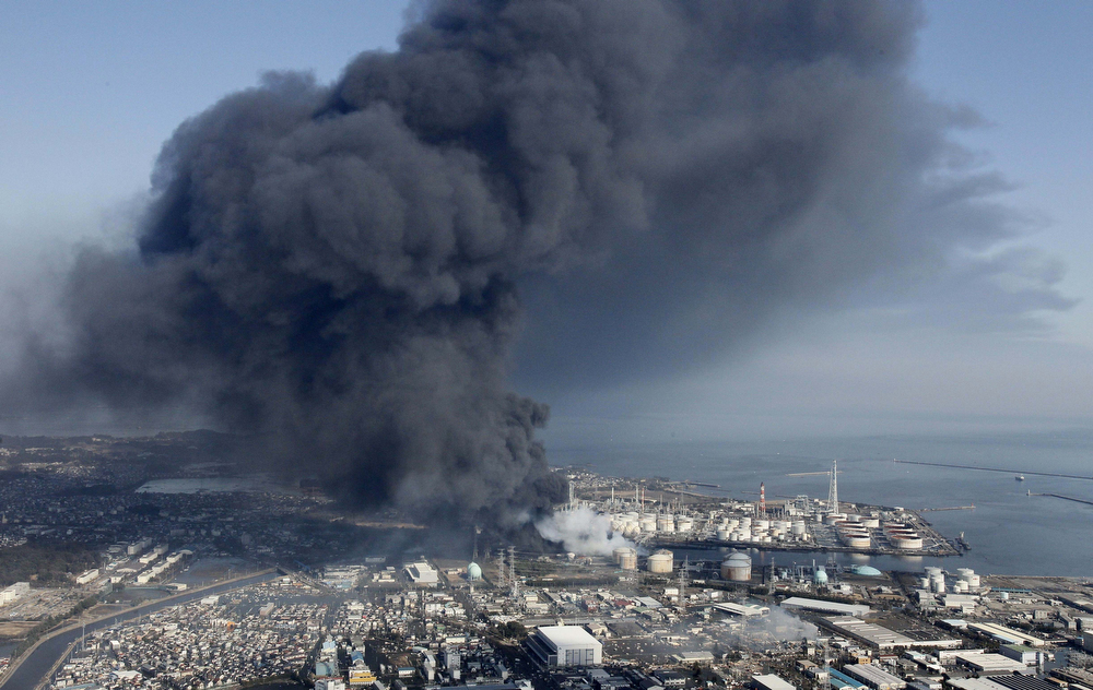 . Black smoke rises from an industrial complex in Shiogama, Miyagi prefecture, northern Japan, Sunday, March 13, 2011, two days after a powerful earthquake and tsunami hit the the country\'s northeastern coast. (AP Photo/Kyodo News)