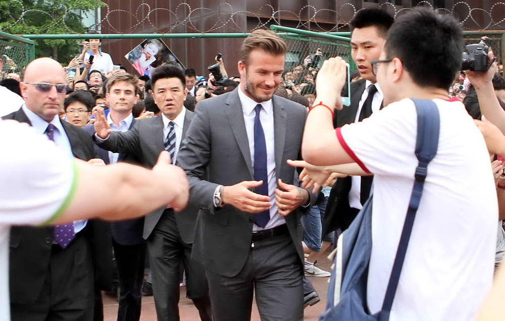 . Football superstar David Beckham (C) is escorted by security personnel at Tonji University in Shanghai on June 20, 2013. Seven people were hurt in a stampede on June 20 as hundreds of fans rushed to see football superstar David Beckham at an event in China\'s commercial hub Shanghai, police and local media said.      AFP PHOTOSTR/AFP/Getty Images