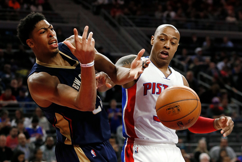. New Orleans Pelicans forward Anthony Davis (23) and Detroit Pistons forward Caron Butler (31) vie for a loose ball during the second half of an NBA basketball game in Auburn Hills, Mich., Wednesday, Jan. 14, 2015. (AP Photo/Paul Sancya)