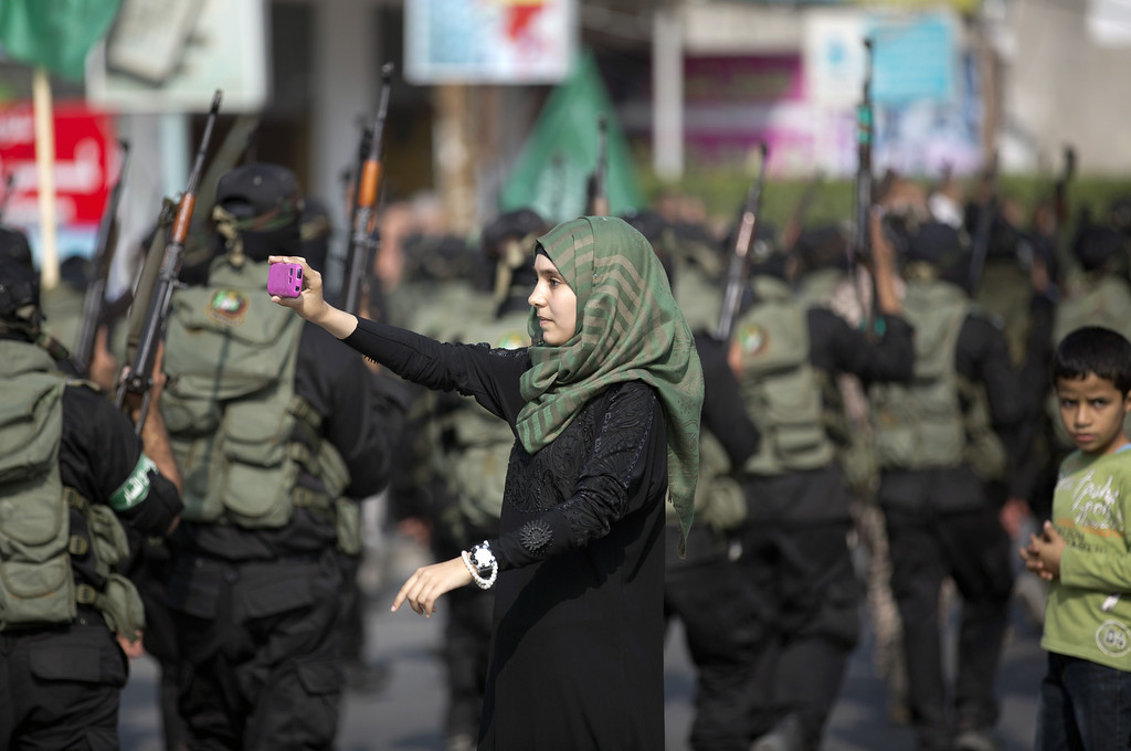 ". A Palestinian girl takes a photo of masked militants of Ezzedine al-Qassam Brigades, Hamas\'s armed wing, using her mobile phone as they parade in Jabalia refugee camp, northern Gaza Strip, on November 14, 2013, during an anti-Israel march as part of the celebrations marking the first anniversary of Israel\'s Operation ""Pillar of Defense\"". AFP PHOTO/MOHAMMED ABED/AFP/Getty Images"