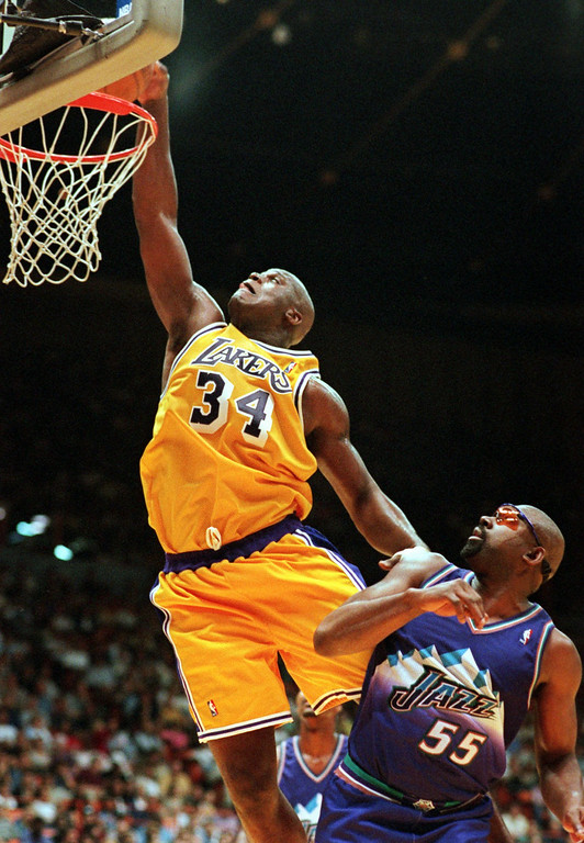. Los Angeles Lakers center Shaquille O\'Neal, left, goes for a dunk as Utah Jazz forward Antoine Carr looks on during the second half of their game Sunday, April 19, 1998, in Inglewood, Calif. O\'Neal scored 33 points to lead the Lakers over Utah, 102-98. (AP Photo/Mark J. Terrill)