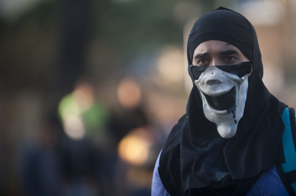 . A demonstrator wears a mask during a protest against the government of Venezuelan President Nicolas Maduro, in Caracas on February 24, 2014. At least 14 people have been killed and 140 others injured in protests nationwide, which have posed the greatest challenge to Venezuelan President Nicolas Maduro\'s government since he was narrowly elected president last year to succeed the late leftist icon Hugo Chavez. (RAUL ARBOLEDA/AFP/Getty Images)