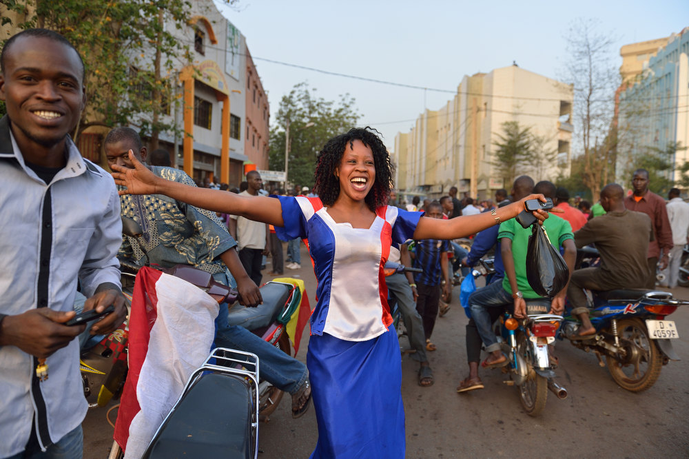 Description of . A woman, wearing a dress with the colors of the French national flag, dances on the Independance square during the visit of French President in Mali on February 2, 2013 in Bamako. French President Francois Hollande called on Africans to take over the fight against extremism as he received a rapturous welcome today in Mali, where a French-led offensive has driven back Islamist rebels from the north. ERIC FEFERBERG/AFP/Getty Images