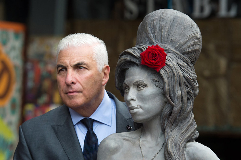 . Mitch Winehouse poses for a picture with a statue of his late daughter, Amy Winehouse after it was unveiled in Camden\'s Stables Market, in London, England, Sunday, Sept. 14, 2014. Three years after her death the unveiling coincides with what would have been her 31st birthday. (AP Photo/Tim Ireland)