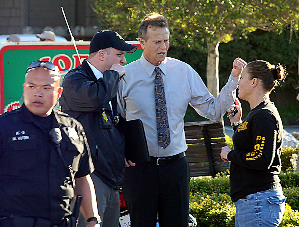 . Santa Cruz County District Attorney Bob Lee confers with  members of the Sheriff\'s Department near the shooting scene Tuesday.  (Dan Coyro/Sentinel)