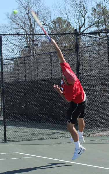 Senior Andrew Veeder serves in a doubles' match against the Trojans of Anderson University.