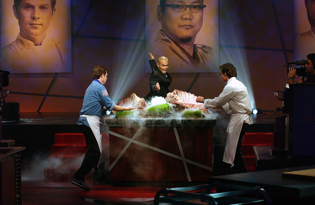". Iron Chef Bobby Flay, left, of Mesa Grill in New York, and challenger Rick Bayless, right, of Frontera Grill in Chicago face off during a taping of the ""Iron Chef America\"" in New York, Oct. 13, 2004. Man in center is unidentified.   (AP Photo/Jim Cooper)"