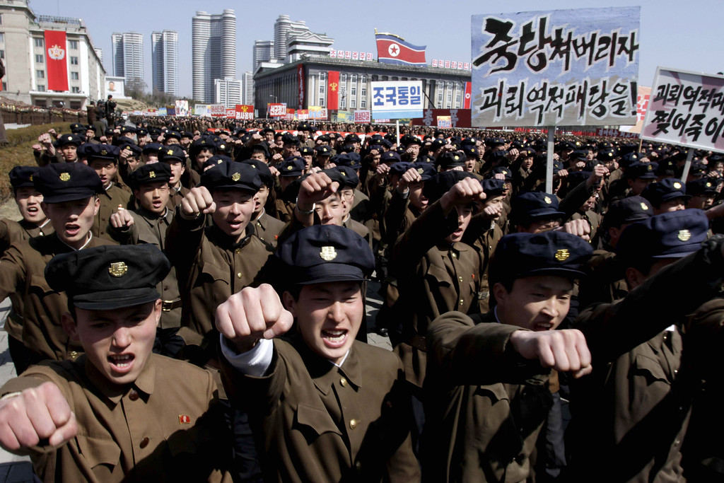 . University students punch the air as they march through Kim Il Sung Square in downtown Pyongyang, North Korea, Friday, March 29, 2013. Tens of thousands of North Koreans turned out for the mass rally at the main square in Pyongyang in support of their leader Kim Jong Un\'s call to arms. Placards read: �Let�s crush the puppet traitor group� and �Let�s rip the puppet traitors to death!� (AP Photo/Jon Chol Jin)