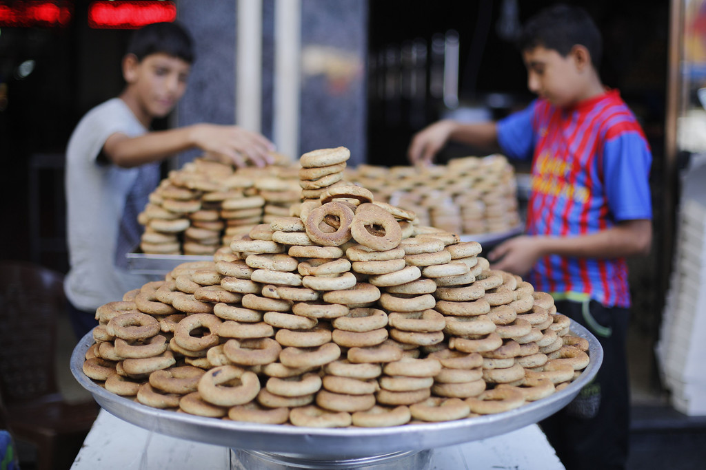 . Palestinian youths display sweets outside a shop in Gaza City on October 3, 2014, on the eve of the Muslim holiday of Eid al-Adha or Feast of the Sacrifice, which marks the end of the annual pilgrimage to Mecca and is celebrated in remembrance of Abraham\'s readiness to sacrifice his son to God. MOHAMMED ABED/AFP/Getty Images