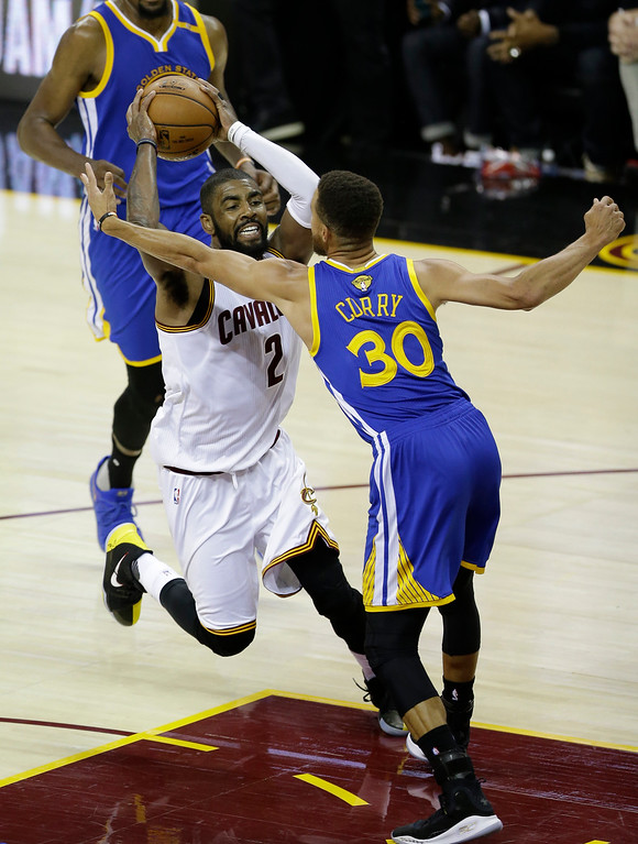 . Cleveland Cavaliers guard Kyrie Irving (2) drives on Golden State Warriors guard Stephen Curry (30) during the second half of Game 3 of basketball\'s NBA Finals in Cleveland, Wednesday, June 7, 2017. (AP Photo/Tony Dejak)