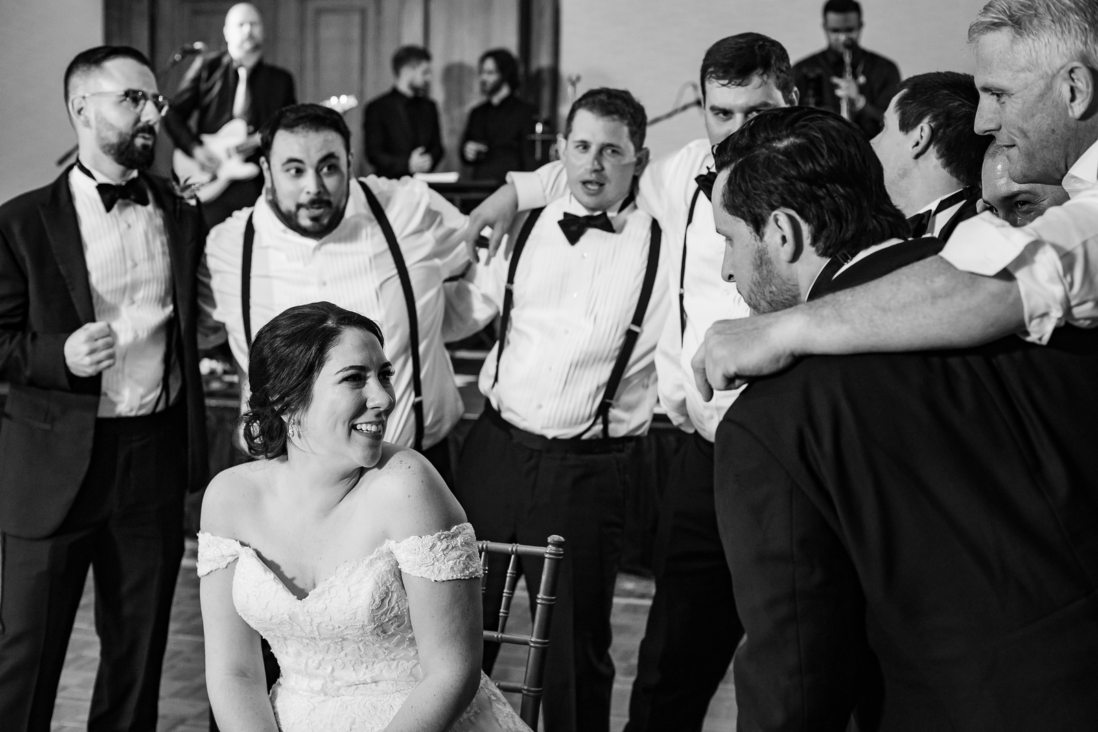 groomsman locking arms in a circle around the bride and singing to her