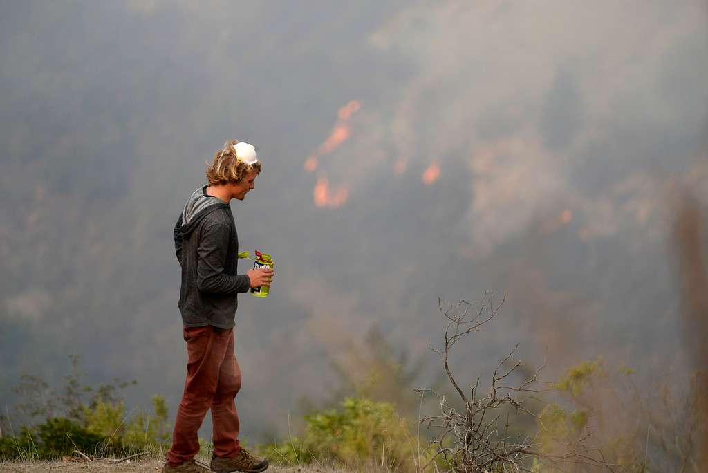 . Garritt Cooper, 25, of Idaho takes a water break while clearing a fire break near a friend\'s home on Rancho Rico Road as firefighters battle a fire across the ridge in the Pfeiffer Ridge area in Big Sur, Calif. on Tuesday December 17, 2013. (Photo David Royal/ Monterey County Herald)