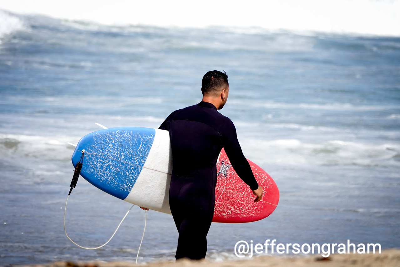 A local surfer heads towards the water for his morning surf in Manhattan Beach