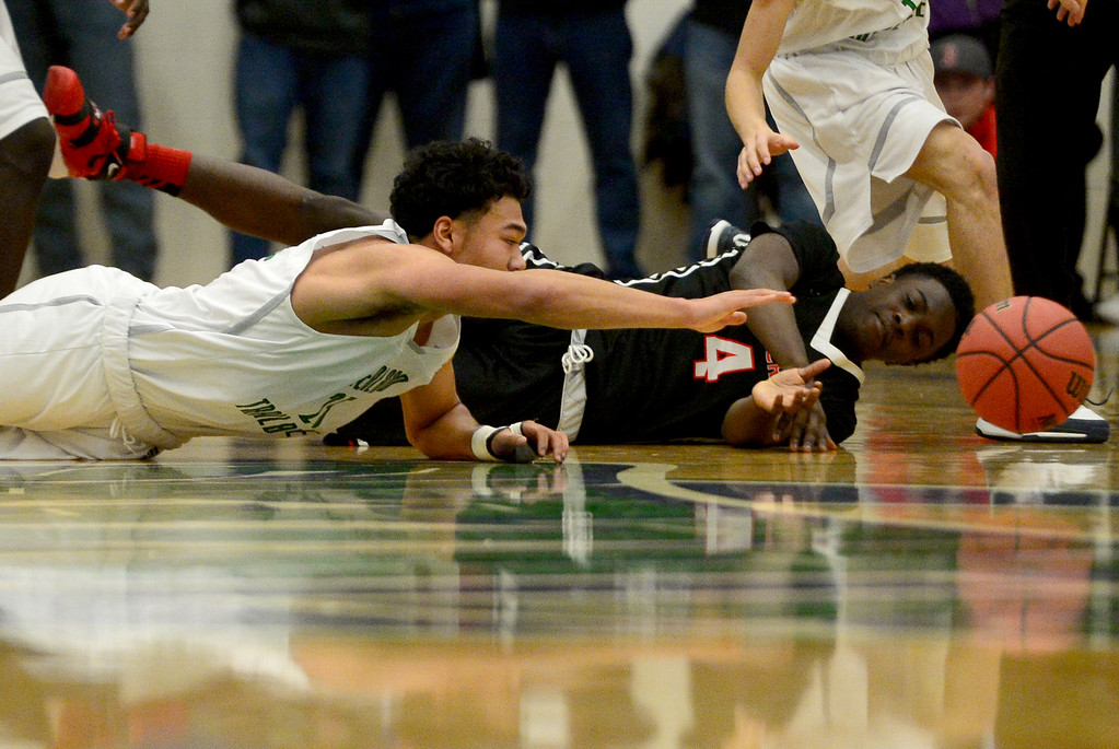 . Xaiv�ion Jackson (4) of EagleCrest  and Tyler Stevenson (25) of Overland dive for a loose ball during the first half of play. The Overland Trailblazers hosted the Eaglecrest Raptors on Friday, January 8, 2016. (Photo by AAron Ontiveroz/The Denver Post)