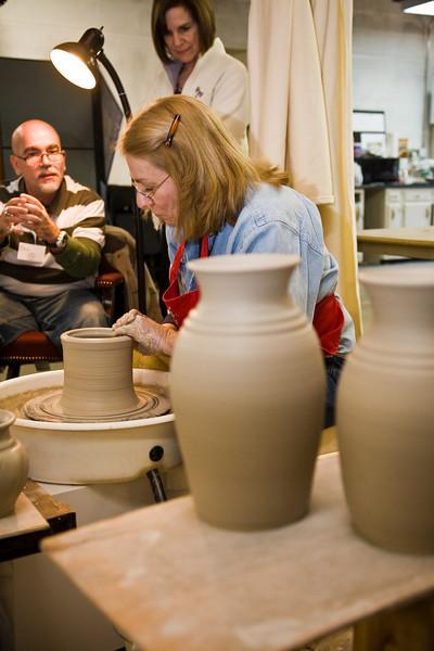 Sylvia Coppola, DuckCreekPottery.com throws a ceramic pot as Carlos Alverez Cotera looks on