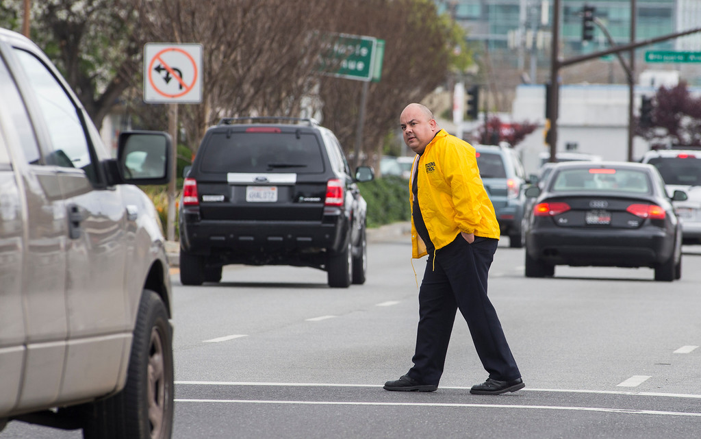 . Steven Diaz, a community service officer with the Redwood City Police Department cautiously crosses El Camino Real at Edwood in Redwood City, Calif., on Wednesday, March 20, 2013. Diaz was part of a county wide program invoving 25 officers from 16 different agencies targeting drivers not stopping for pedestrians in the cross walk and excessive speed. About 200 citations were handed out on Wednesday. (John Green/Staff)