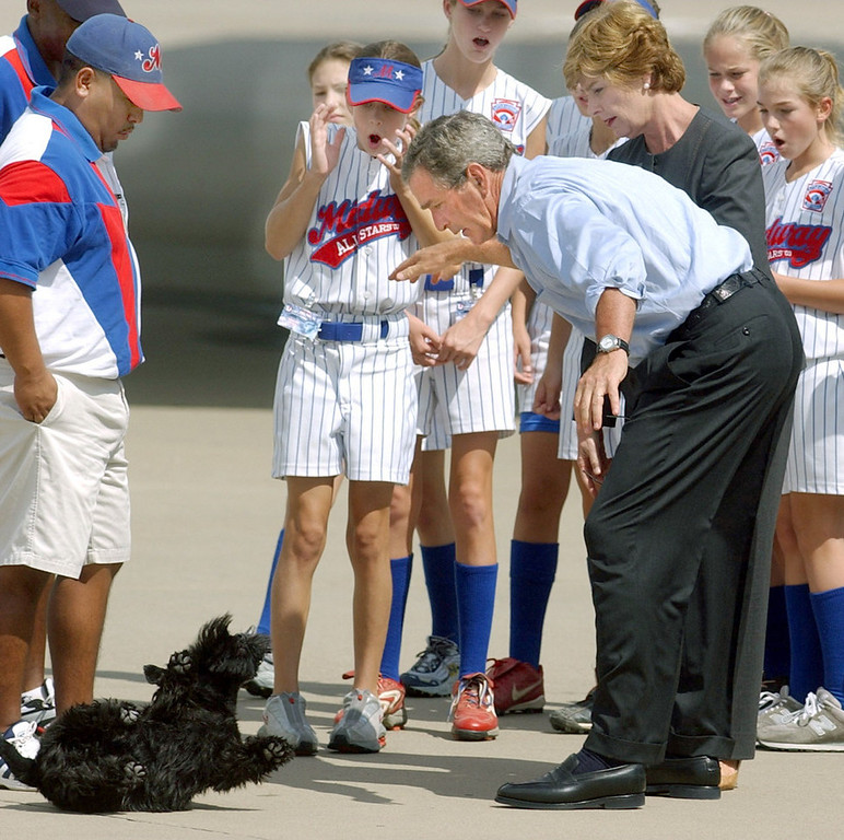 . President Bush, along with first lady, Laura Bush, and members of the Waco Midway Little League Softball World Series championship team, react as Bush accidentally drops his dog, Barney, Saturday, Aug. 30, 2003, at TSTC Airfield in Waco, Texas. Bush quickly scooped up the dog who was not injured. (AP Photo/Duane A. Laverty)