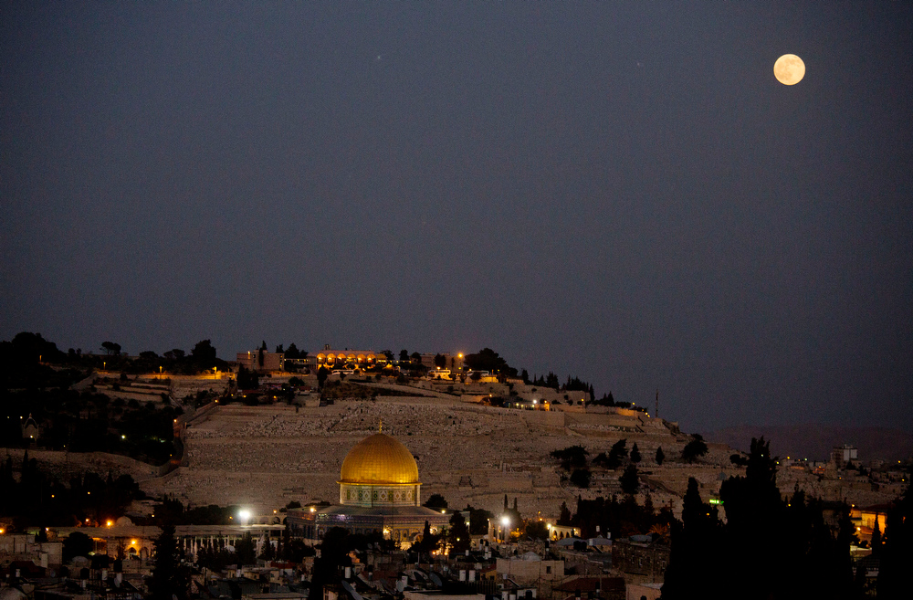 . A supermoon rises over Jerusalem\'s Old City and the Dome of the Rock Saturday, July 12, 2014. A supermoon is an occurrence when a full moon is closest to the Earth in its orbit. (AP Photo/Dusan Vranic)