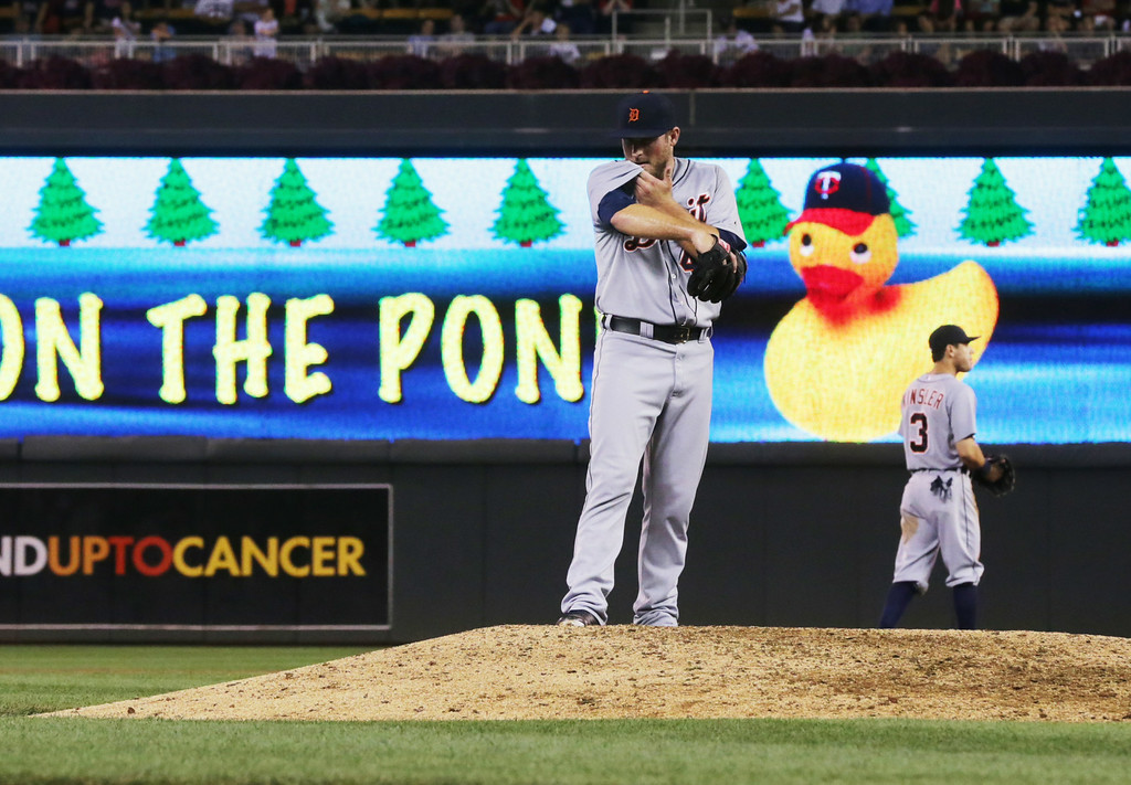 . Detroit Tigers pitcher Ian Krol wipes his face after giving up a walk to Minnesota Twins first baseman Kennys Vargas  to load the bases in the sixth inning of a baseball game, Friday, Aug. 22, 2014, in Minneapolis. (AP Photo/Jim Mone)