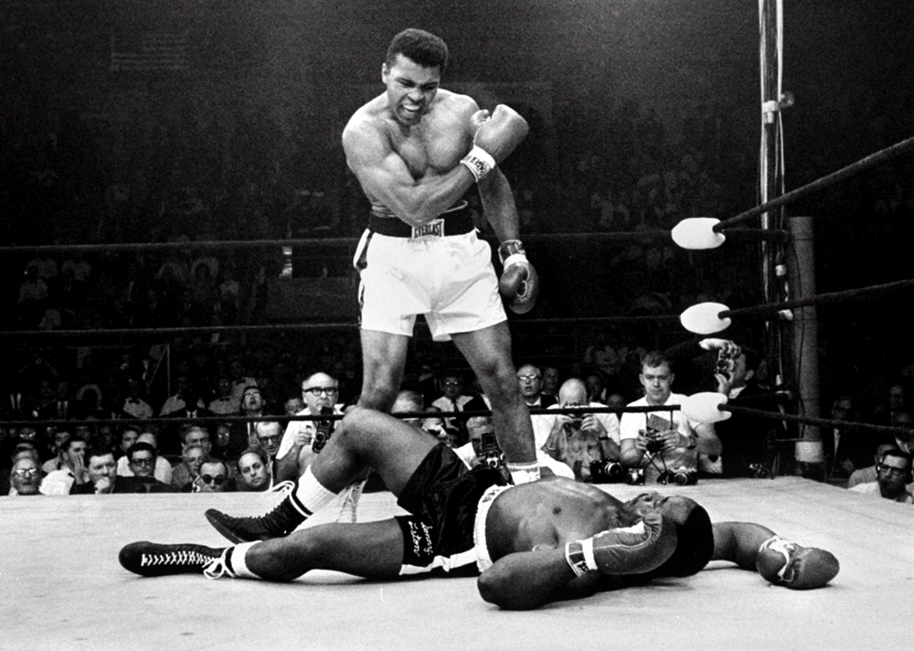 Description of . Heavyweight champion Muhammad Ali, then known as Cassius Clay, stands over fallen challenger Sonny Liston, shouting and gesturing shortly after dropping Liston with a short hard right to the jaw on May 25, 1965, in Lewiston, Maine.   The bout lasted only one minute into the first round.  Ali is the only man ever to win the world heavyweight boxing championship three times.  He also won a gold medal in the  light-heavyweight division at the 1960 Summer Olympics in Rome as a member of the U.S. Olympic boxing team.   (AP Photo/John Rooney)