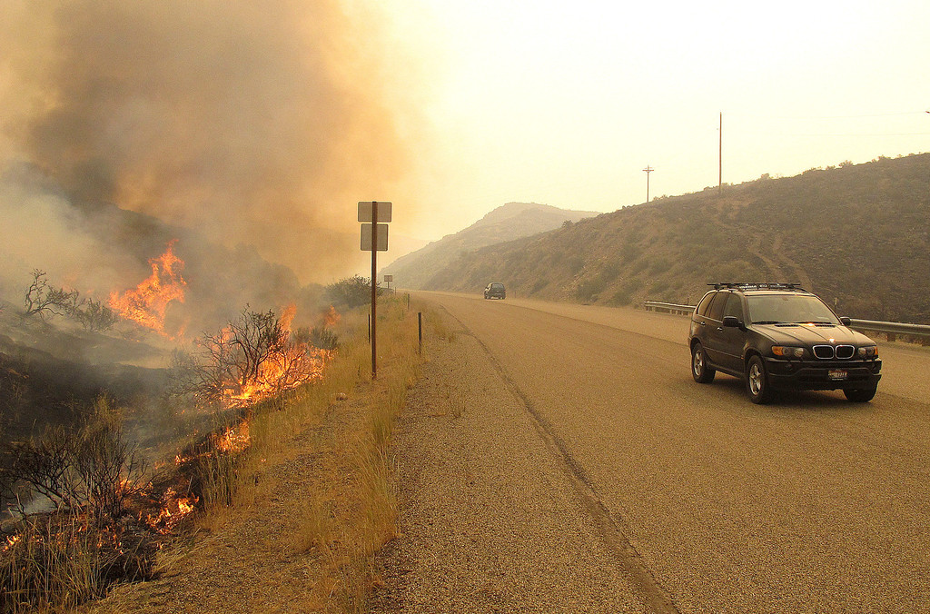 . A fire burns on the shoulder of U.S. Highway 20 north of Mountain Home, Idaho on Monday, Aug. 12, 2013. The blaze was among several touched off in recent days by a lightning storm that rolled through the region.  (AP Photo/John Miller)