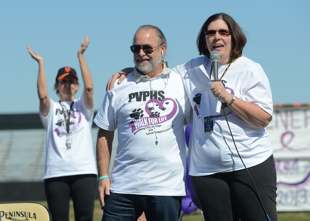 . Hundreds of Peninsula High School students took part in the school\'s Walk for Life on Wednesday which raises money for cancer research and awareness.  Principal Mitzi Cress, right, leads the ceremony with the husband of Peggy Hescox; one of the three people the cancer walk was dedicated to. 20130227 Photo by Steve McCrank / Staff Photographer