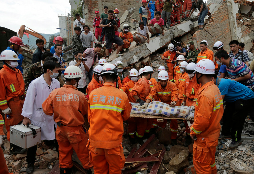 . Rescuers prepare to carry away a young victim on a stretcher near a destroyed house following a massive earthquake in the town of Longtoushan in Ludian County in southwest China\'s Yunnan Province Tuesday, Aug. 5, 2014. (AP Photo/Andy Wong)