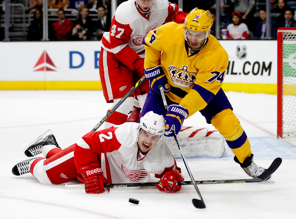 . Los Angeles Kings left wing Dwight King, top, knocks Detroit Red Wings defenseman Brendan Smith to the ice during the second period of an NHL hockey game in Los Angeles, Tuesday, Feb. 24, 2015. (AP Photo/Chris Carlson)