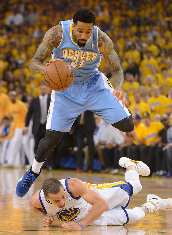 . Wilson Chandler (21) of the Denver Nuggets leaps over Stephen Curry (30) of the Golden State Warriors during the first quarter in Game 6 of the first round NBA Playoffs May 2, 2013 at Oracle Arena. (Photo By John Leyba/The Denver Post)