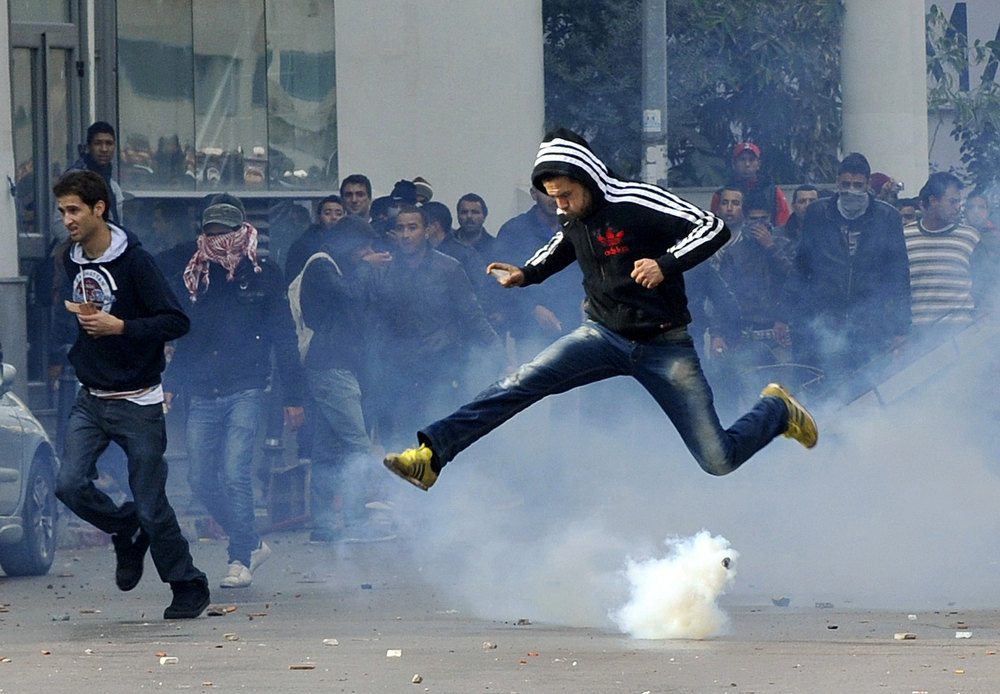 . A Tunisian protester jumps amid smoke after police fired tear gas during a rallye outside the Interior ministry to protest after Tunisian opposition leader and outspoken government critic Chokri Belaid was shot dead with three bullets fired from close range, on February 6, 2013 in Tunis. The protesters, who massed on Habib Bourguiba Avenue, epicentre of the 2011 uprising that ousted ex-dictator Zine El Abidine Ben Ali, pelted the police with bottles and the police responded by firing tear gas, chasing the protesters and beating them with batons. FETHI BELAID/AFP/Getty Images