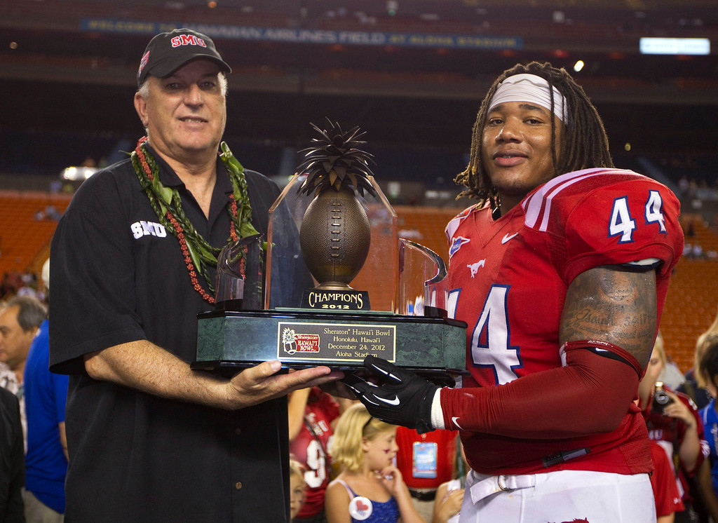 . SMU coach June Jones and linebacker Taylor Reed (44) hold the Hawaii Bowl trophy after SMU defeated Fresno State 43-10 in the college football game Monday, Dec. 24, 2012, in Honolulu. (AP Photo/Eugene Tanner)