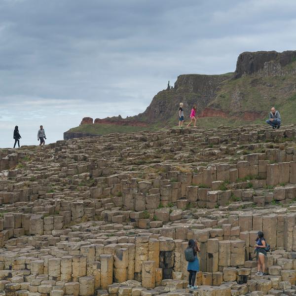Tourists walking on basalt rocks, Giants Causeway, County Antrim, Northern Ireland, United Kingdom