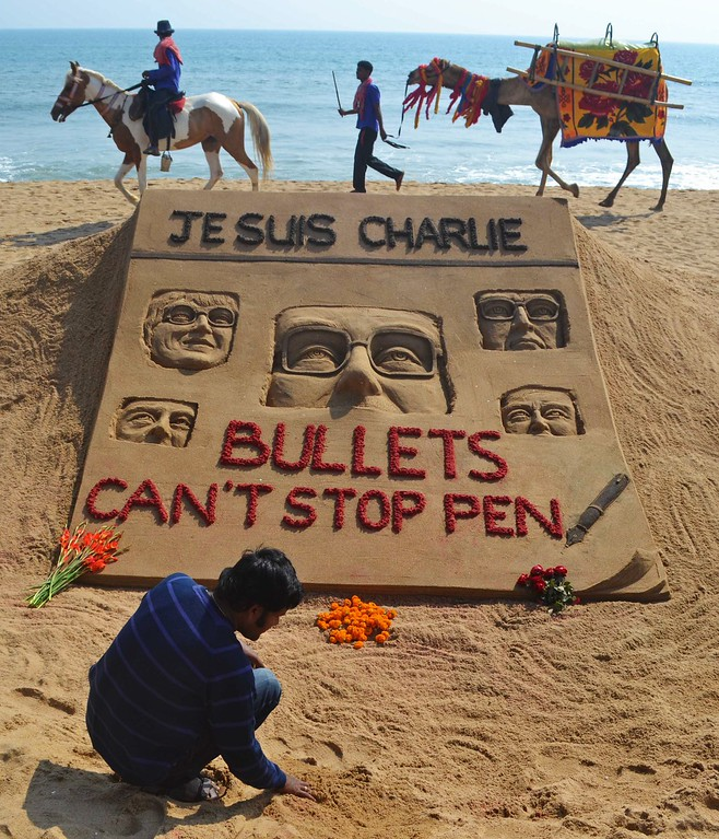 . Indian artist Sudarsan Pattnaik is pictured with his sand sculpture, in tribute of those who lost their lives in the January 7 attack by gunmen on French satirical weekly Charlie Hebdo in Paris that killed 12 people, at Golden Sea Beach in Puri, some 65 kilometers from Bhubaneswar, on January 8, 2015. A stunned and outraged France began a national day of mourning January 8, as security forces desperately hunted two brothers suspected of gunning down 12 people in an Islamist assault on a satirical weekly, the country\'s bloodiest attack in half a century. AFP PHOTO / ASIT KUMAR/AFP/Getty Images