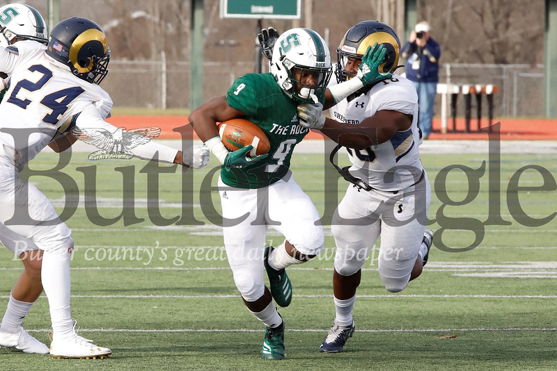 Slippery Rock wide reciever Jermaine Wynn Jr.  stiff arms a Shepherd University defender after a reception in Saturday's 51-30 playoff win. Seb Foltz/Butler Eagle