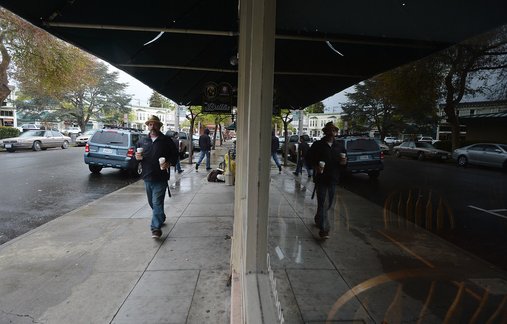 . Beverage in hand, a Starbuck\'s patron walks along Park Place in the Point Richmond area of Richmond, Calif. on Thursday, Feb. 7, 2013. (Kristopher Skinner/Staff)