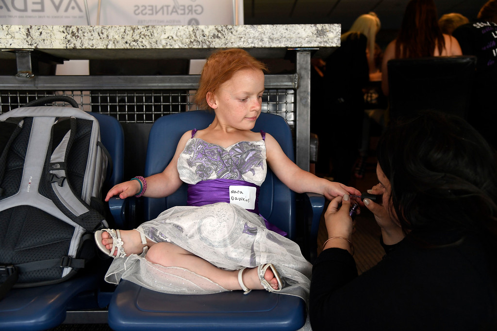 . Mara Dawkins, 13, gets her nails done by Bella Martin as she gets ready from prom. Teens get their makeup, hair and nails done before prom night May 13, 2016 at Sports Authority Field at Mile High. The teen patients had a treat as they got to meet with Denver Broncos quarterback Mark Sanchez who was on hand to greet them. Some of the teens missed their own prom due to illness and just couldn\'t attend. Childrens Hospital hosted the Night of Champions gala. (Photo By John Leyba/The Denver Post)