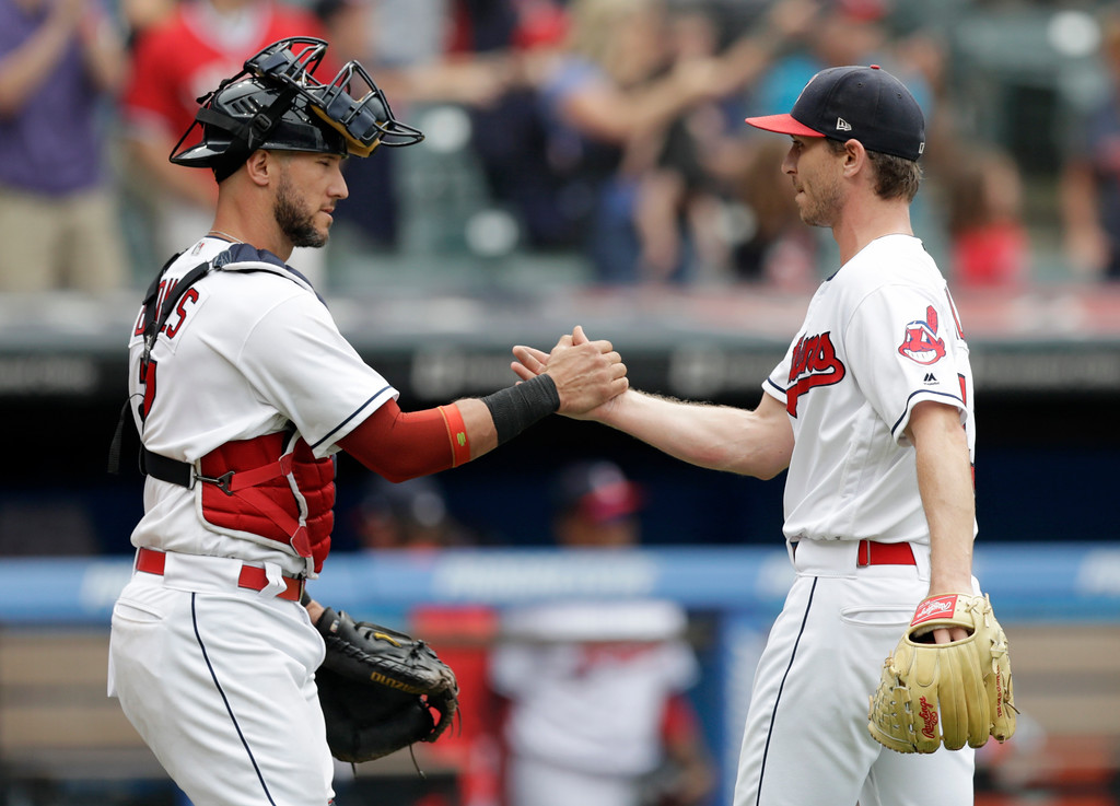 . Cleveland Indians\' Yan Gomes, left, and relief pitcher Josh Tomlin celebrate after the Indians defeated the Chicago White Sox 12-0 in a baseball game, Wednesday, June 20, 2018, in Cleveland. (AP Photo/Tony Dejak)