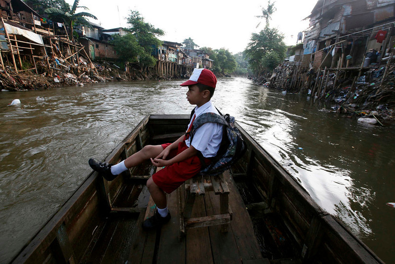 . A boy sits in a wooden boat transporting him across a river to go to school in Jakarta June 5, 2013. Local residents say that they are highly dependent on the river due to their lack of shower, washing and toilet facilities. World Environment Day is celebrated annually on June 5.  REUTERS/Enny Nuraheni