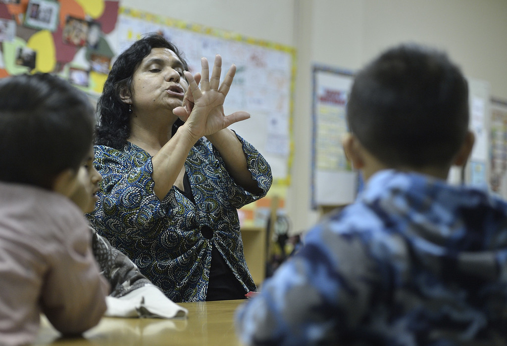 . LONG BEACH, CALIF. USA -- Assistant teacher Maria Navarro works on counting with students at Pine Head Start in Long Beach, Calif., on February 25, 2013.  Photo by Jeff Gritchen / Los Angeles Newspaper Group