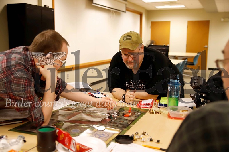 Stephen Wilbert oversees Chris Griebel make a move in the local role playing game Kysie Returned  -- a Dungeons and Dragons style  role playing game-- during  Tabletop Game Day at the Butler Area Public Library Saturday. Seb Foltz/Butler Eagle