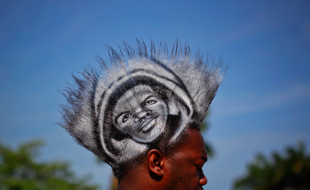 ". A man, who identified himself as Mohawk Gaz, sports an image of black teenager Trayvon Martin on his hair during a rally to protest his killing in Miami, Florida April 1, 2012. Thousands of protesters gathered in a downtown bayfront park on Sunday demanding the arrest of the neighborhood watch volunteer who shot and killed an unarmed black teenager, Trayvon Martin, in central Florida a month ago. ""Trayvon Martin shooting\"" ranked as Google\'s ninth most searched trending event of 2012. REUTERS/Lucas Jackson"