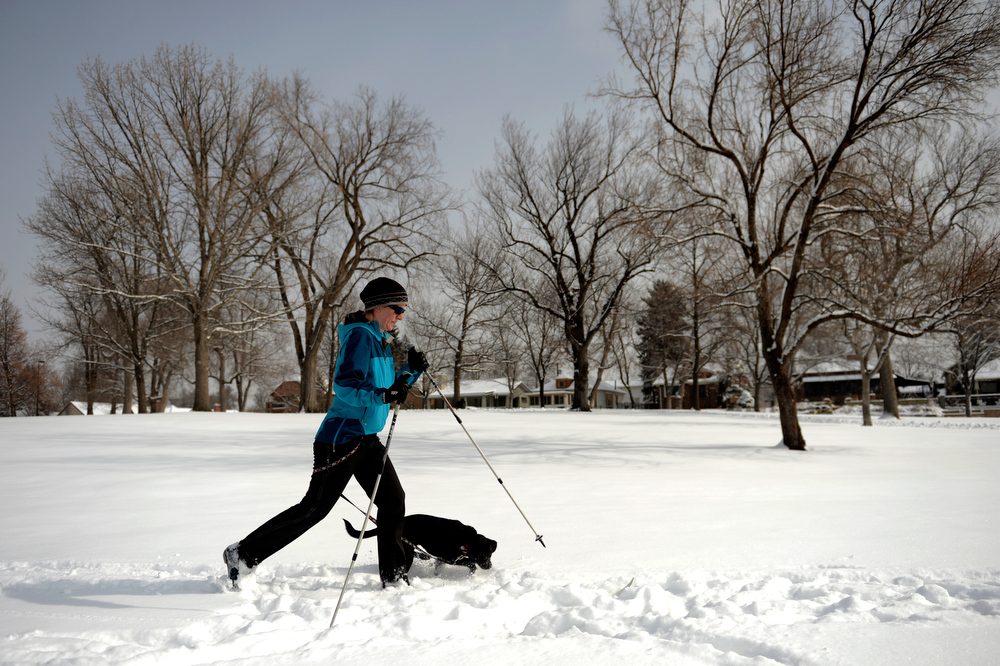 . Meghan Chandler of Edgewater eats up ground on her cross country skis when she isn\'t tangled with her dog Kea at Sloan\'s Lake after an over night snow fall left 3 to 6 inches across Denver and the surrounding areas February 21, 2013. Denver, Colorado. (Photo By Joe Amon/The Denver Post)