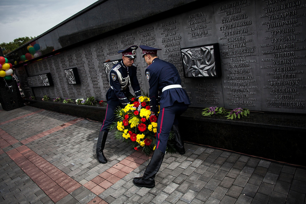 . Ukrainian police officers lay a bouquet of flowers by a monument in memory of those fallen in WWII during the commemoration of Victory Day in Donetsk, Ukraine, Friday, May 9, 2014.  (AP Photo/Manu Brabo)