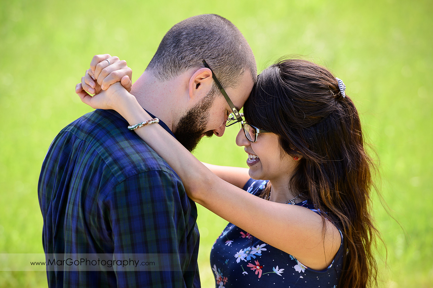 close-up portrait of man in blue shirt and woman in blue dress touching foreheads on the green grass backround during engagement session at Sunol Regional Wilderness
