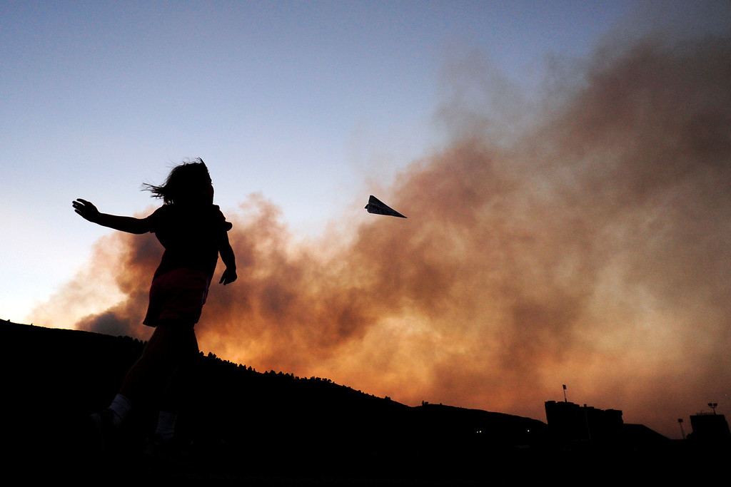 . Charlotte Frank, 8, throws a paper airplane while on a walk with her father near Hughes Stadium as the High Park Fire burns west of Fort Collins on Sunday, June 17, 2012. AAron Ontiveroz, The Denver Post