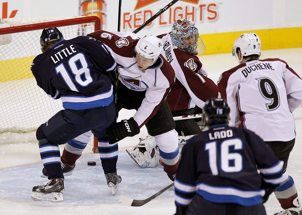 . Winnipeg Jets\' Blake Wheeler\'s (26) shot gets past Colorado Avalanche goaltender Semyon Varlamov (1) as Jets\' Bryan Little (18) and Avalanche\'s Erik Johnson (6) fight for position during first period NHL hockey action in Winnipeg, Manitoba, on Thursday, Dec. 12, 2013. (AP Photo/The Canadian Press, John Woods)