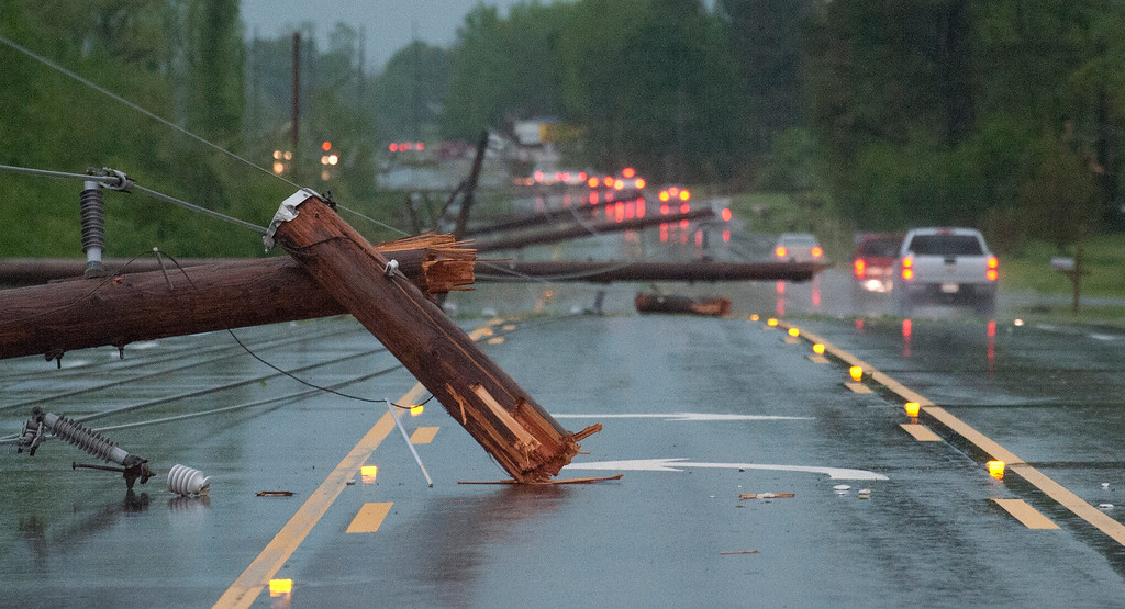 . Downed utility poles lie across a road in the Clements community west of Athens, Ala., after a tornado on Monday, April 28, 2014. Local officials reported six deaths in Alabama from the tornado. State emergency officials could not immediately confirm those deaths. Thousands of customers were without power in Alabama and Kentucky, where severe storms caused widespread damages. (AP Photo/The Decatur Daily, Brennen Smith)
