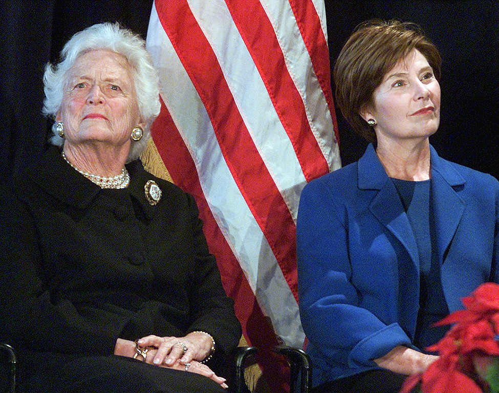 . Former first lady Barbara Bush, left, and first lady Laura Bush look on before introducing the opening of the White House Visitors Center exhibit in Washington Sunday, Dec. 9, 2001. The exhibit gives tourists an idea what the executive mansion looks like during the holidays, as the White House is closed to tours this season for security reasons. (AP Photo/Rick Bowmer)